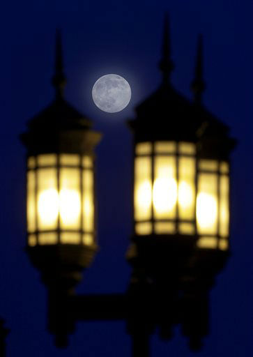 A full moon rises through a hazy sky over street lamps, Saturday, June 22, 2013, in Baltimore. The moon, which will reach its full stage on Sunday, is expected to be 13.5 percent closer to earth during a phenomenon known as supermoon. &#40;AP Photo&#47;Patrick Semansky&#41; <span class=meta>(AP Photo&#47; Patrick Semansky)</span>