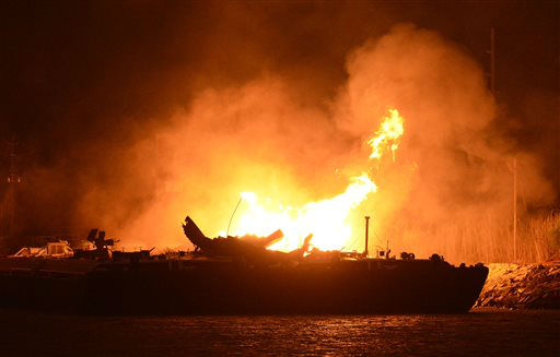 A massive explosion at 3 a.m. EDT on one of the two barges still ablaze in the Mobile River in Mobile, Ala., on Thursday, April 25, 2013. Three people were injured in the blast. Fire officials have pulled units back from fighting the fire due to the explosions and no immediate threat to lives. &#40;AP Photo John David Mercer&#41; Three people were hospitalized with burns. Information on their conditions was not immediately available. <span class=meta>(AP Photo&#47; John David Mercer)</span>