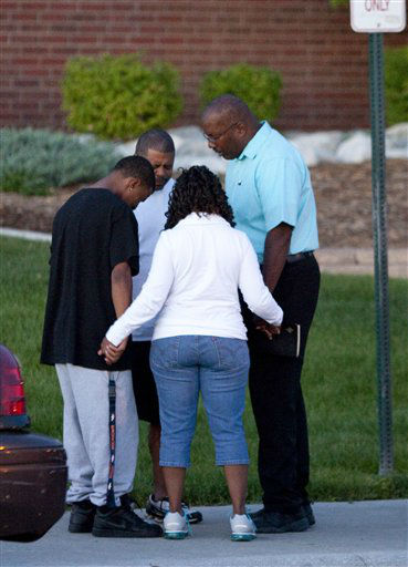 A small group prays outside Gateway High School where witness were brought for questioning Friday, July 20, 2012 in Aurora, Colo.  A gunman wearing a gas mask set off an unknown gas and fired into the crowded movie theater killing 12 people and injuring at least 50 others, authorities said. &#40;AP Photo&#47;Barry Gutierrez&#41; <span class=meta>(AP Photo&#47; Barry Gutierrez)</span>