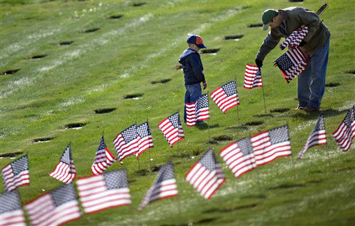 Joseph Manning, right, of Raynham, Mass., and his son Joey, 6, a Cub Scout, place U.S. flags at the graves of deceased veterans at the National Cemetery in Bourne, Mass., Saturday, Nov. 10, 2012.  Thousands of flags were placed in the cemetery in advance of Veterans Day. &#40;AP Photo&#47;Gretchen Ertl&#41; <span class=meta>(AP Photo&#47; Gretchen Ertl)</span>