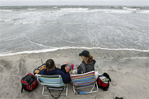 George Barats, of Levittown, Pa., and Michele Scheid, of Bristol, Pa., sit on the edge of a churning Atlantic Ocean Saturday, Oct. 27, 2012, in North Wildwood, N.J., as Hurricane Sandy begins to show its effects. From the lowest lying areas of the Jersey shore, where residents were already being encouraged to leave, to the state&#39;s northern highlands, where sandbags were being filled and cars moved into parking lots on high ground, New Jersey began preparing in earnest for Hurricane Sandy. &#40;AP Photo&#47;Mel Evans&#41; <span class=meta>(AP Photo&#47; Mel Evans)</span>