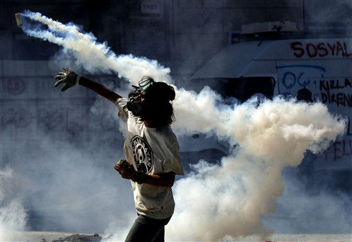 "<div class=""meta ""><span class=""caption-text "">A protester throws back to police a tear gas canister during clashes in Taksim square in Istanbul, Tuesday, June 11, 2013. Hundreds of police in riot gear forced through barricades in Istanbul's central Taksim Square early Tuesday, pushing many of the protesters who had occupied the square for more than a week into a nearby park. (AP Photo/Kostas Tsironis) (AP Photo/ Kostas Tsironis)</span></div>"