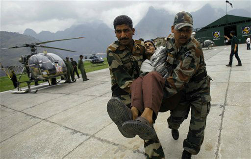 An injured Indian pilgrim cries in pain as Indian army soldiers carry him after he was rescued from the higher reaches of mountains at a makeshift helipad at Joshimath, in northern Indian state of Uttarakhand, Monday, June 24, 2013. A top official said the death toll in northern India could rise as army soldiers clear the debris from towns and villages flattened by landslides and monsoon flooding. Home Minister Sushilkumar Shinde said the number of people who have perished in the floods that washed away thousands of homes could go beyond the 1,000 deaths reported so far. &#40;AP Photo&#47;Rafiq Maqbool&#41; <span class=meta>(AP Photo&#47; Rafiq Maqbool)</span>