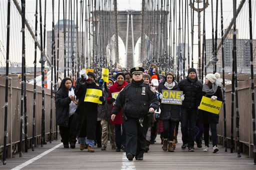 A NYPD officer leads demonstrators over the Brooklyn bridge towards downtown Manhattan during a One Million Moms for Gun Control Rally, Jan. 21, 2012, in New York. Demonstrators called for new gun control legislation, demanding a ban on assault weapons and stricter regulations on gun purchases. The One Million Moms for Gun Control group formed in the wake of last month&#39;s massacre at a Connecticut elementary school. &#40;AP Photo&#47;John Minchillo&#41; <span class=meta>(AP Photo&#47; John Minchillo)</span>