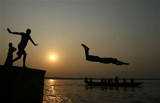 An Indian boy dives into the River Ganges, as tourists ride a boat in Varanasi, India,  Thursday, Sept. 27, 2012.  Varanasi is among the world&#39;s oldest cities, and millions of Hindu pilgrims gather annually here for ritual bathing and prayers in the Ganges river considered holiest by Hindus. &#40;AP Photo&#47;Rajesh Kumar Singh&#41; <span class=meta>(AP Photo&#47; Rajesh Kumar Singh)</span>