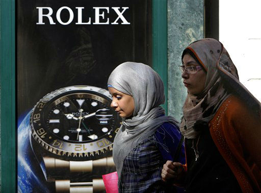 Egyptians walk in front of an advertisement for a watch in Cairo, Egypt, Monday, March 25, 2013. Egypt&#39;s Islamist President Mohammed Morsi has hiked customs rates on dozens of &#34;unnecessary&#34; imports, including watches, as part of the government&#39;s efforts to increase revenues to revive the ailing economy. &#40;AP Photo&#47;Amr Nabil&#41; <span class=meta>(AP Photo&#47; Amr Nabil)</span>