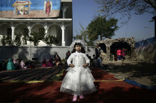 Pakistani Anusha Khalid, 4, dressed as a bride, poses for a picture at an outdoor Mass on Christmas Day, in a Christian neighborhood in Islamabad, Pakistan, Tuesday, Dec. 25, 2012. &#40;AP Photo&#47;Muhammed Muheisen&#41; <span class=meta>(AP Photo&#47; Muhammed Muheisen)</span>