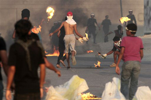 Bahraini anti-government protesters carrying petrol bombs face off against riot police firing tear gas and stun grenades in Sadad, Bahrain, on Wednesday, Oct. 3, 2012. Clashes erupted at the end of a mourning procession for Ali Hussein Niema, 17, who allegedly was shot dead last week by riot police. &#40;AP Photo&#47;Hasan Jamali&#41; <span class=meta>(AP Photo&#47; Hasan Jamali)</span>