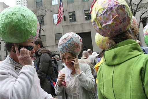 Wearing paper mache Easter eggs on their heads, Joe Marshall, left, and his wife Terry Marshall, foreground second from left, from Plymouth, Mass., talk on their phones as they and other members of their family, wearing similar hats, take part in the Easter Parade Sunday March 31, 2013 on New York's Fifth Avenue.