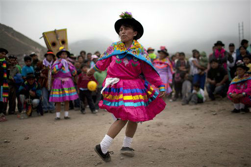 A woman performs an indigenous dance called Huaylia at the Virgen de Lourdes cemetery where relatives converge to honor friends and family who have passed, marking the Day of the Dead holiday, in Lima, Peru, Thursday, Nov. 1, 2012. The holiday honors the deceased on Nov. 1, coinciding with All Saints Day and All Souls&#39; Day on Nov. 2. &#40;AP Photo&#47;Rodrigo Abd&#41; <span class=meta>(AP Photo&#47; Rodrigo Abd)</span>