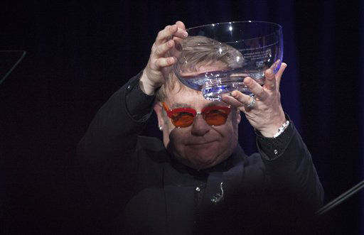 Elton John holds up an award during the AIDS Foundation&#39;s 12th Annual &#34;An Enduring Vision&#34; benefit gala at Cipriani Wall Street on Tuesday, Oct. 15, 2013 in New York. &#40;Photo by Carlo Allegri&#47;Invision&#47;AP&#41; <span class=meta>(Photo&#47;Carlo Allegri)</span>