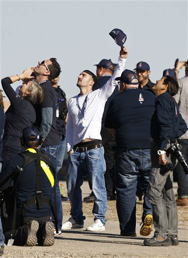 An onlooker waves as he and others watch the capsule carrying Felix Baumgartner lifts off as he attempts to break the speed of sound with his own body by jumping from a space capsule lifted by a helium balloon, Sunday, Oct. 14, 2012, in Roswell, N.M.  Baumgartner plans to jump from an altitude of 120,000 feet, an altitude chosen to enable him to achieve Mach 1 in free fall, which would deliver scientific data to the aerospace community about human survival from high altitudes.&#40;AP Photo&#47;Ross D. Franklin&#41; <span class=meta>(AP Photo&#47; Ross Franklin)</span>