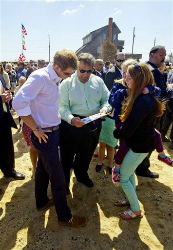 Britain&#39;s Prince Harry and N.J. Gov. Chris Christie look at a before photo of  a home that belongs to the Bowden family home which is now empty lot in Mantoloking, N.J. on Tuesday, May 14, 2013.  Prince Harry began a tour Tuesday of New Jersey?s storm-damaged coastline, inspecting dune construction, walking past destroyed homes and shaking hands with police and other emergency workers.  &#40;AP Photo&#47;The Star-Ledger, Andrew Mills, Pool&#41; <span class=meta>(AP Photo&#47; Andrew Mills)</span>