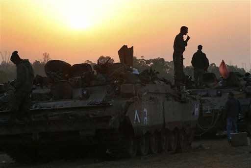 The sun rises as an Israeli soldier washes his teeth atop a tank that he slept on, at a staging area near the Israel Gaza Strip Border, southern Israel, early Tuesday, Nov. 20, 2012. On Tuesday, grieving Gazans were burying militants and civilians killed in ongoing Israeli airstrikes, and barrages of rockets from Gaza sent terrified Israelis scurrying to take cover. Efforts to end a week-old convulsion of Israeli-Palestinian violence drew in the world's top diplomats Tuesday, with U.S. President Barack Obama dispatching his secretary of state to the region on an emergency mission and the U.N. chief appealing from Cairo for an immediate cease-fire. (AP Photo/Lefteris Pitarakis)