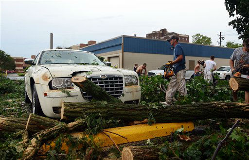 "<div class=""meta ""><span class=""caption-text "">People work en masse to break-up felled trees and free cars underneath them in Elmira N.Y., after a severe storm in the area, Thursday, July 26, 2012. Power lines and trees were toppled and hospitals were placed on disaster alert but there were no immediate reports of injuries after a possible tornado hit the city of Elmira Thursday afternoon, Chemung County Office of Fire and Emergency Management spokeswoman Karen Miner said. (AP photos/Heather Ainsworth) (AP Photo/ Heather Ainsworth)</span></div>"