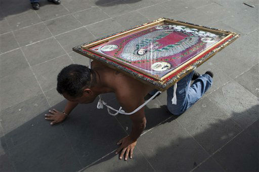A man crawls carrying an image of the Virgin of Guadalupe on his back as he approaches the entrance to the Basilica of Guadalupe in Mexico City, Tuesday, Dec. 11, 2012.  Nationwide, devotees of the Virgin of Guadalupe make a pilgrimage to the Basilica in honor of her Dec. 12 feast day. &#40;AP Photo&#47;Eduardo Verdugo&#41; <span class=meta>(AP Photo&#47; Eduardo Verdugo)</span>