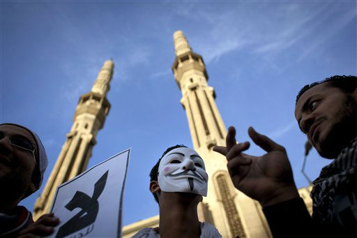 Protesters opposing Egyptian President Mohammed Morsi, one wears a Guy Fawkes mask, chant slogans during a demonstration that started in front of el-Nour mosque, background, in Cairo, Egypt, Tuesday, Dec. 11, 2012. Thousands of opponents and supporters of Egypt&#39;s Islamist president staged rival rallies in the nation&#39;s capital Tuesday, four days ahead a nationwide referendum on a contentious draft constitution.&#40;AP Photo&#47;Nasser Nasser&#41; <span class=meta>(AP Photo&#47; Nasser Nasser)</span>