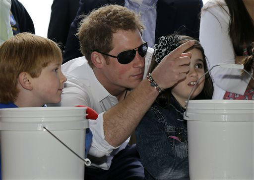 "<div class=""meta ""><span class=""caption-text "">Michael Vanover, 7, left, looks on as Britain's Prince Harry helps Taylor Cirigliano, 11, right, pick a prize at a Ball Toss game on the boardwalk,  while visiting the area hit by Superstorm Sandy, Tuesday, May 14, 2013, in Seaside Heights, N.J.  Prince Harry began a tour  of New Jersey?s storm-damaged coastline, inspecting dune construction, walking past destroyed homes and shaking hands with police and other emergency workers.  New Jersey sustained about $37 billion worth of damage from the storm. (AP Photo/Mel Evans) (AP Photo/ Mel Evans)</span></div>"