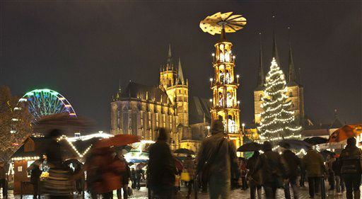 People walk at a Christmas Market during heavy rain in front of the Mariendom &#40;Cathedral of Mary&#41;, left,  and St. Severi&#39;s Church, right, in Erfurt, central Germany, Wednesday, Nov. 28, 2012. The Erfurt Christmas Market is one of the most beautiful Christmas Markets in Germany. The square is  decorated with a huge, candle-lit Christmas tree and a large, hand-carved nativity scene. &#40;AP Photo&#47;Jens Meyer&#41; <span class=meta>(AP Photo&#47; JENS MEYER)</span>