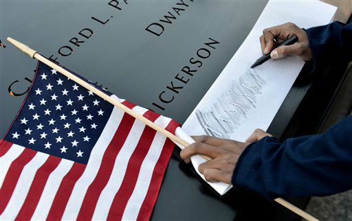 "<div class=""meta image-caption""><div class=""origin-logo origin-image ""><span></span></div><span class=""caption-text"">Alicia Watkins of Washington, D.C., makes a rubbing of a friend's name at the South Pool of the World Trade Center Memorial during the 11th anniversary observance of the 9/11 terrorist attacks in New York, Tuesday, Sept. 11, 2012. (AP Photo/Justin Lane, Pool) (AP Photo/ Justin Lane)</span></div>"
