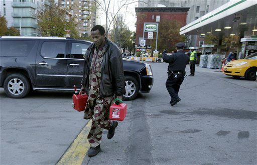 A man carries two filled gas cans at a gasoline station, in New York, Friday, Nov. 9, 2012. A new gasoline rationing plan that lets motorists fill up every other day went into effect in New York on Friday morning. Police were at gas stations to enforce the new system in New York City and on Long Island.  &#40;AP Photo&#47;Richard Drew&#41; <span class=meta>(AP Photo&#47; Richard Drew)</span>