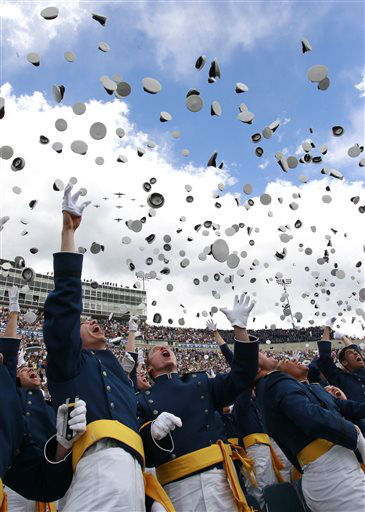 Graduating Air Force 2nd Lieutenants throw their caps into the air at the completion of the commencement ceremony for the class of 2013, at the U.S. Air Force Academy, in Colorado, Wednesday May 29, 2013.  In the background, a group of WWII warplanes do a flyover.&#40;AP Photo&#47;Brennan Linsley&#41; <span class=meta>(AP Photo&#47; Brennan Linsley)</span>