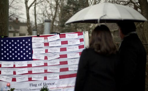 Mourners looks at the names on a U.S. flag of the Sandy Hook Elementary School shooting victims at a sidewalk memorial, Sunday, Dec. 16, 2012, in Newtown, Conn.A gunman walked into Sandy Hook Elementary School in Newtown Friday and opened fire, killing 26 people, including 20 children.  &#40;AP Photo&#47;David Goldman&#41; <span class=meta>(AP Photo&#47; David Goldman)</span>