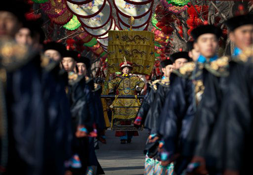 A Chinese actor dressed as Qing Dynasty emperor, center, sits on a sedan chair during a rehearsal of an ancient Qing Dynasty ceremony ahead of the upcoming Chinese New Year at Ditan Park in Beijing Friday, Feb. 8, 2013. Chinese will celebrate the Lunar New Year on Feb. 10 this year which marks the Year of Snake. &#40;AP Photo&#47;Andy Wong&#41; <span class=meta>(AP Photo&#47; Andy Wong)</span>