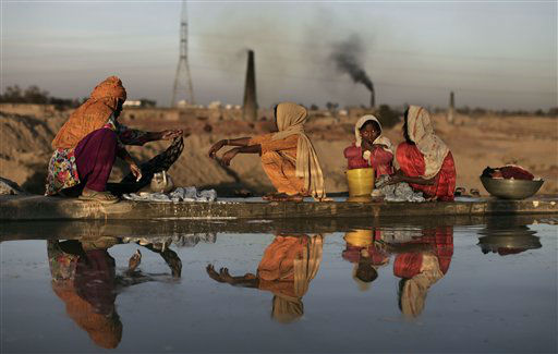 A Pakistani woman and her daughters wash their laundry at a water reservoir on the outskirts of Rawalpindi, Pakistan, Thursday, March 7, 2013. Pakistan will mark the International day for women with other nations on Friday, March 8. &#40;AP Photo&#47;Muhammed Muheisen&#41; <span class=meta>(AP Photo&#47; Muhammed Muheisen)</span>