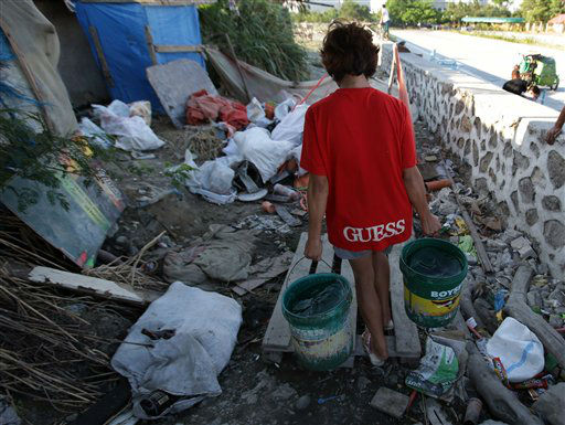 "<div class=""meta ""><span class=""caption-text "">In this March 12, 2013 photo, a Filipino woman carries buckets of water along a filthy pathway at a slum in suburban Pasay, south of Manila, Philippines. Ninety-one percent of people living in Asia have improved access to clean water, a remarkable achievement over the last two decades in the world's most populous region. But its richest countries and wealthiest citizens likely have better water supplies and governments better prepared for natural disasters. (AP Photo/Aaron Favila) (AP Photo/ Aaron Favila)</span></div>"