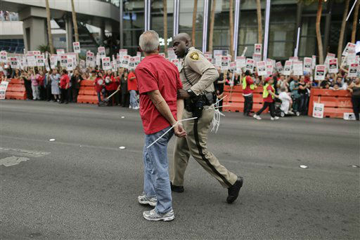 A Las Vegas Metropolitan Police officer leads away a protestor during a civil disobedience demonstration by Culinary Union workers outside the Cosmopolitan Hotel-Casino, Wednesday, March 20, 2013, in Las Vegas. Nearly 98 protestors were arrested during the demonstration in which they sat on and blocked traffic along Las Vegas Boulevard. Workers have been in contract talks with Cosmopolitan Las Vegas owner Deutsche  Bank for two years.  &#40;AP Photo&#47;Julie Jacobson&#41; <span class=meta>(AP Photo&#47; Julie Jacobson)</span>