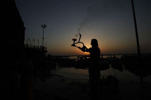 A Hindu priest rotates a traditional oil lamp in circular movements as he performs morning prayers on the banks of the Ganges River in Varanasi, India, early Wednesday morning, Sept. 26, 2012.  Varanasi is among the world&#39;s oldest cities, where millions of Hindu pilgrims gather annually for ritual bathing and prayers in the Ganges River,  considered holiest by Hindus. &#40;AP Photo&#47;Rajesh Kumar Singh&#41; <span class=meta>(AP Photo&#47; Rajesh Kumar Singh)</span>