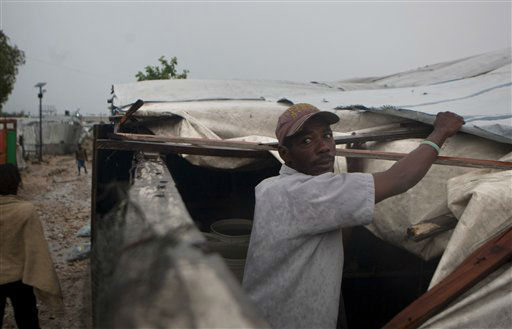 A man works to repair the roof of his tent in a camp for people displaced by the 2010 earthquake as Tropical Storm Isaac affects Port-au-Prince, Haiti, Saturday, Aug. 25, 2012. Tropical Storm Isaac swept across Haiti&#39;s southern peninsula early Saturday, dousing a capital city prone to flooding and adding to the misery of a poor nation still trying to recover from the 2010 earthquake. &#40;AP Photo&#47;Dieu Nalio Chery&#41; <span class=meta>(AP Photo&#47; Dieu Nalio Chery)</span>