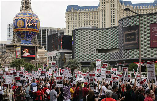 Culinary Union workers demonstrate along Las Vegas Boulevard outside the Cosmopolitan Hotel and Casino while protesting their contract negotiations with Deutsche Bank, Wednesday, March 20, 2013, in Las Vegas. Nearly 98 protestors were arrested during the demonstration. Workers have been in contract talks with Cosmopolitan Las Vegas owner Deutsche  Bank for two years. &#40;AP Photo&#47;Julie Jacobson&#41; <span class=meta>(AP Photo&#47; Julie Jacobson)</span>
