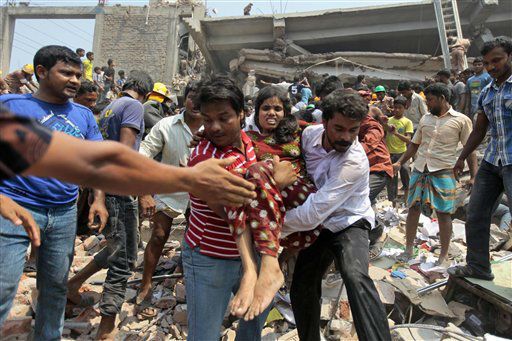 "<div class=""meta image-caption""><div class=""origin-logo origin-image ""><span></span></div><span class=""caption-text"">Rescuers assist an injured woman after an eight-story building housing several garment factories collapsed in Savar, near Dhaka, Bangladesh, Wednesday, April 24, 2013. Dozens were killed and many more are feared trapped in the rubble. (AP Photo/ A.M. Ahad) (AP Photo/ A.M. Ahad)</span></div>"
