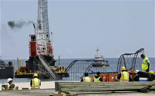 "<div class=""meta ""><span class=""caption-text "">Workers watch from the new boardwalk they are building in Seaside Heights, N.J., Monday, May 13, 2013, as a huge crane works  to dismantle the Jet Star Roller Coaster which has been sitting in the ocean after part of the Casino Pier was destroyed during Superstorm Sandy. The work began Tuesday afternoon after Great Britain's Prince Harry ended a visit there. (AP Photo/Mel Evans) (AP Photo/ Mel Evans)</span></div>"