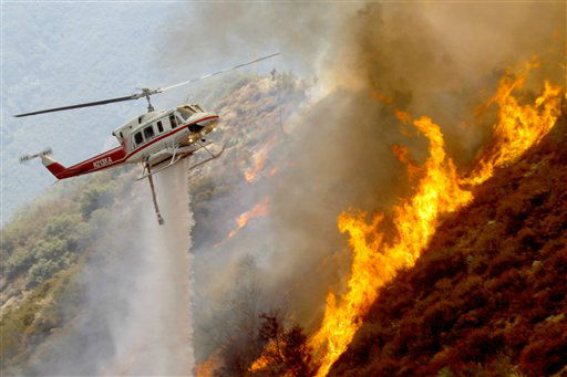 A Los Angeles County Firefighter helicopter drops water on a wildfire burning through 3,600 acres of the Angeles National Forest on Tuesday Sept. 4, 2012 near Glendora, Calif. It could be a week before firefighters can contain the blaze because of high temperatures and rugged terrain in thick brush that hasn&#39;t burned in a couple of decades. &#40;AP Photo&#47;Nick Ut&#41; <span class=meta>(AP Photo&#47; Nick Ut)</span>