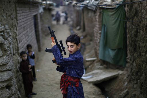 An Afghan refugee boy poses with a plastic rifle as he and other children celebrate the first day of the Eid al-Fitr festival, which marks the end of the Muslim fasting month of Ramadan, in a slum on the outskirts of Islamabad, Pakistan, Monday, Aug. 20, 2012. Muslims around the world are celebrating Eid al-Fitr, marking the end of Ramadan, the Muslim calendar&#39;s ninth and holiest month during which followers are required to abstain from food and drink from dawn to dusk. &#40;AP Photo&#47;Muhammed Muheisen&#41; <span class=meta>(AP Photo&#47; Muhammed Muheisen)</span>
