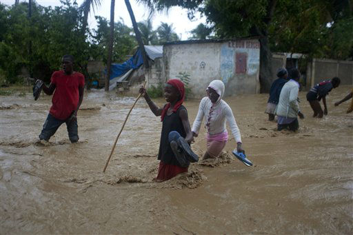 Residents cross a street that flooded due to Tropical Storm Isaac in Port-au-Prince, Haiti, Saturday, Aug. 25, 2012. Tropical Storm Isaac swept across Haiti&#39;s southern peninsula early Saturday, dousing a capital city prone to flooding and adding to the misery of a poor nation still trying to recover from the terrible 2010 earthquake. &#40;AP Photo&#47;Dieu Nalio Chery&#41; <span class=meta>(AP Photo&#47; Dieu Nalio Chery)</span>