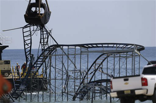 The claw of a crane, left, tears through the structure of the Jet Star Roller Coaster, Tuesday, May 14, 2013, in Seaside Heights, N.J. Workers began to demolish the roller coaster, which fell in the ocean when part of the Casino Pier was washed away by Superstorm Sandy in October. &#40;AP Photo&#47;Julio Cortez&#41; <span class=meta>(AP Photo&#47; Julio Cortez)</span>
