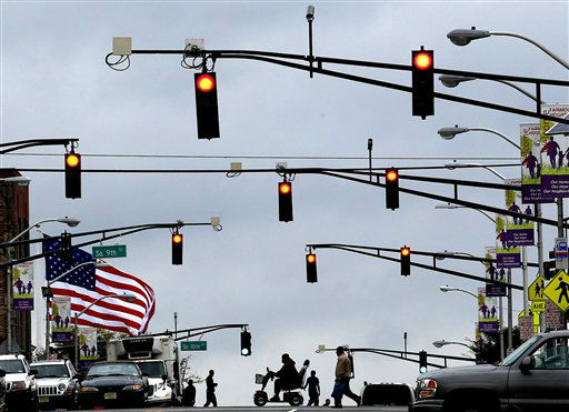 A large U.S. flag, left, waves in gusty winds and pedestrians cross the street under red streetlights in Newark, N.J. on Tuesday, Sept. 18, 2012. A tornado watch has been issued for parts of New Jersey, New York City and New York&#39;s lower Hudson Valley until 7 p.m. The National Weather Service Storm Prediction Center says lightning, hail and wind gusts up to 70 mph are possible. &#40;AP Photo&#47;Julio Cortez&#41; <span class=meta>(AP Photo&#47; Julio Cortez)</span>