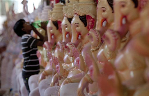 A worker drinks water near to the idols of Hindu elephant headed god Ganesh in Mumbai, India, Wednesday, Aug. 22, 2012. The idols will be immersed in the Arabian Sea at the end of the ten day long Ganesh festival which begins on September 19. &#40;AP Photo&#47; Rajanish Kakade&#41; <span class=meta>(AP Photo&#47; Rajanish Kakade)</span>
