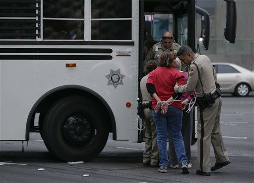 A Las Vegas Metropolitan Police officer checks the pockets of a protestor before loading her onto a bus during a civil disobedience demonstration by the Culinary Workers Union outside the Cosmopolitan Hotel-Casino, Wednesday, March 20, 2013, in Las Vegas. Nearly 98 protestors were arrested during the demonstration in which they sat on and blocked traffic along Las Vegas Boulevard. Workers have been in contract talks with Cosmopolitan Las Vegas owner Deutsche  Bank for two years. &#40;AP Photo&#47;Julie Jacobson&#41; <span class=meta>(AP Photo&#47; Julie Jacobson)</span>