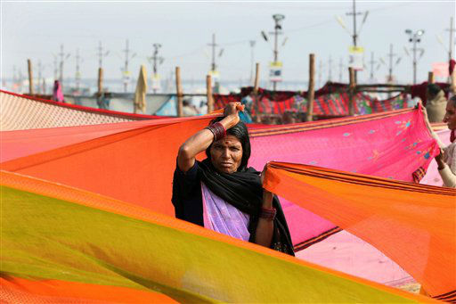 An Indian Hindu devotee dries her clothes after taking a dip in Sangam, the confluence of the Ganges, Yamuna and mythical Saraswati River, during the Maha Kumbh festival, in Allahabad, India, Thursday, Feb. 7, 2013. Millions of Hindu pilgrims are attending the Maha Kumbh festival, which is one of the world's largest religious gatherings that lasts 55 days and falls every 12 years. During the festival pilgrims bathe in the holy Ganges River in a ritual they believe can wash away their sins. (AP Photo/Manish Swarup)