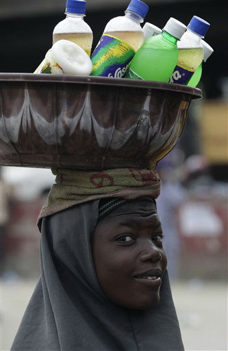A girl hawks soft drinks at a bus park, on the first International Day of the Girl Child, in Lagos, Nigeria, Thursday, Oct. 11, 2012. The UN declared October 11 as the International Day of the Girl Child, to recognize girls? rights and the unique challenges girls face around the world. &#40;AP Photo&#47;Sunday Alamba&#41; <span class=meta>(AP Photo&#47; Sunday Alamba)</span>
