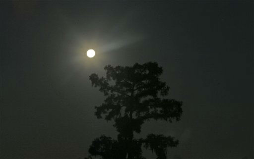 The larger-than-normal full moon referred to as Supermoon sets beyond a tree near fishing camps in Akers, La., Sunday, June 23, 2013. &#40;AP Photo&#47;Gerald Herbert&#41; <span class=meta>(AP Photo&#47; Gerald Herbert)</span>