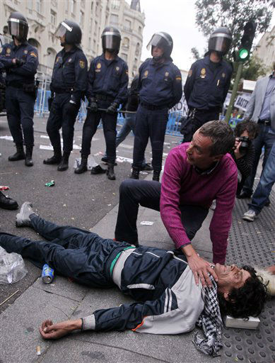A protestor lies on the ground after a clash with police during the march to the parliament against austerity measures announced by the Spanish government in Madrid, Spain, Tuesday, Sept. 25, 2012.  The demonstration, organized behind the slogan &#39;Occupy Congress,&#39; was expected to draw thousands of people.  Madrid authorities said some 1,300 police would be deployed. The protestors call for Parliament to be dissolved and fresh elections held, claiming the government&#39;s austerity measures show the ruling Popular Party misled voters to get elected last November. &#40;AP Photo&#47;Andres Kudacki&#41; <span class=meta>(AP Photo&#47; Andres Kudacki)</span>