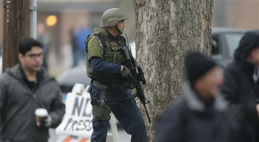 A Conn. State Police tactical team officer takes cover behind a tree as the area around St. Rose of Lima Catholic Church is searched in Newtown, Conn., Sunday, Dec. 16, 2012 after a there was a bomb threat. A gunman opened fire at Sandy Hook Elementary School in the town, killing 26 people, including 20 children before killing himself on Friday. &#40;AP Photo&#47;Charles Krupa&#41; <span class=meta>(AP Photo&#47; Charles Krupa)</span>