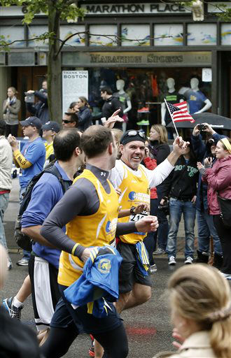Runners who were unable to finish the Boston Marathon on April 15 because of the bombings pass the first bombing site as they head toward the finish line on Boylston Street after the city allowed them to finish the last mile of the race in Boston Saturday, May 25, 2013. &#40;AP Photo&#47;Winslow Townson&#41; <span class=meta>(AP Photo&#47; Winslow Townson)</span>