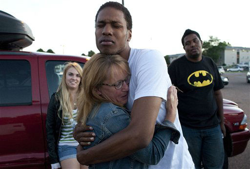 Judy Goos, second from left, hugs her daughters friend,  Isaiah Bow, 20, while eye witnesses Emma Goos, 19, left, and Terrell Wallin, 20, right, gather outside Gateway High School where witness were brought for questioning Friday, July 20, 2012 in Denver.   A gunman wearing a gas mask set off an unknown gas and fired into a crowded movie theater at a midnight opening of the Batman movie &#34;The Dark Knight Rises,&#34; killing at least 12 people and injuring at least 50 others, authorities said. &#40;AP Photo&#47;Barry Gutierrez&#41; <span class=meta>(AP Photo&#47; Barry Gutierrez)</span>